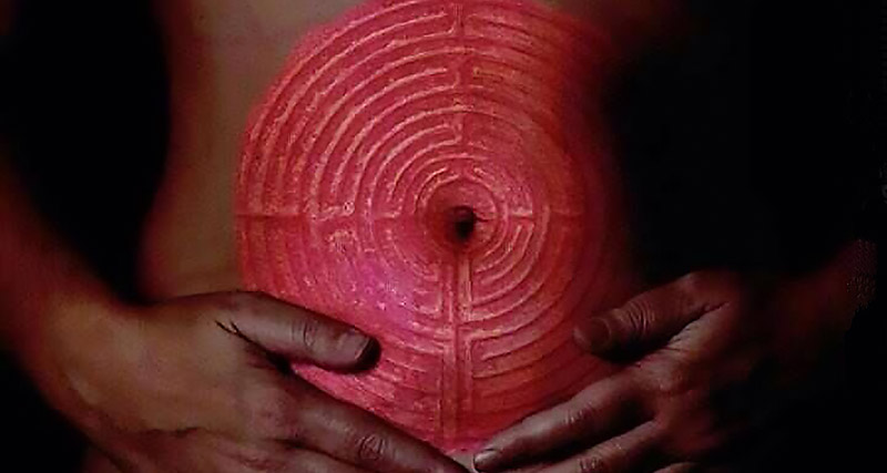 Red Labyrinth on a Woman's Belly and she is holding her womb